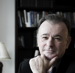 Headshot of Professor Marks against a dark backdrop of a bookcase.