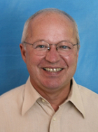 Headshot of Professor Ron Rindfuss against a blue background.