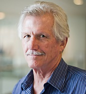 Headshot of Professor Stephens against the backdrop of the inside of the Global Education Center at UNC.