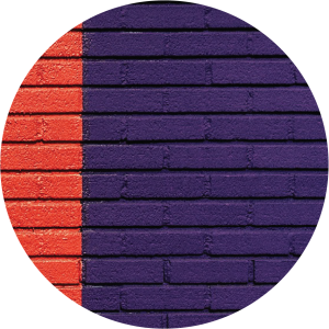 Decorative circular image of brick wall painted red and dark blue with clear contrasting straight line where the two colors meet.