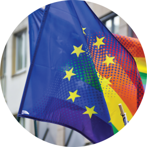 Decorative circular photo of two flags where the EU's flag blends into the Pride flag.