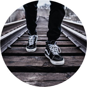 Decorative circular photo of legs and sneakers on a railroad track.