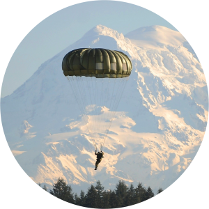 Decorative photo of paratrooper with snowy mountains in the background.