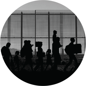 Decorative circular image with silhouettes of people carrying luggage walking in front of a high fence.
