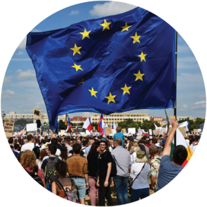 Decorative circular image of a crowd with EU and Polish flags and a big EU flag held up and taking up most of the top half of the photo.